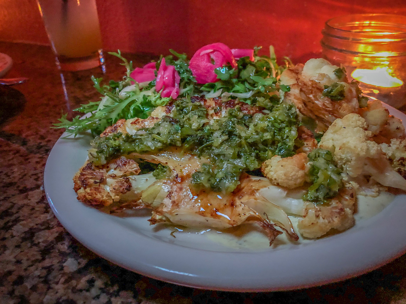 Thick slice of roasted cauliflower on a plate topped with green salsa and pickled onions