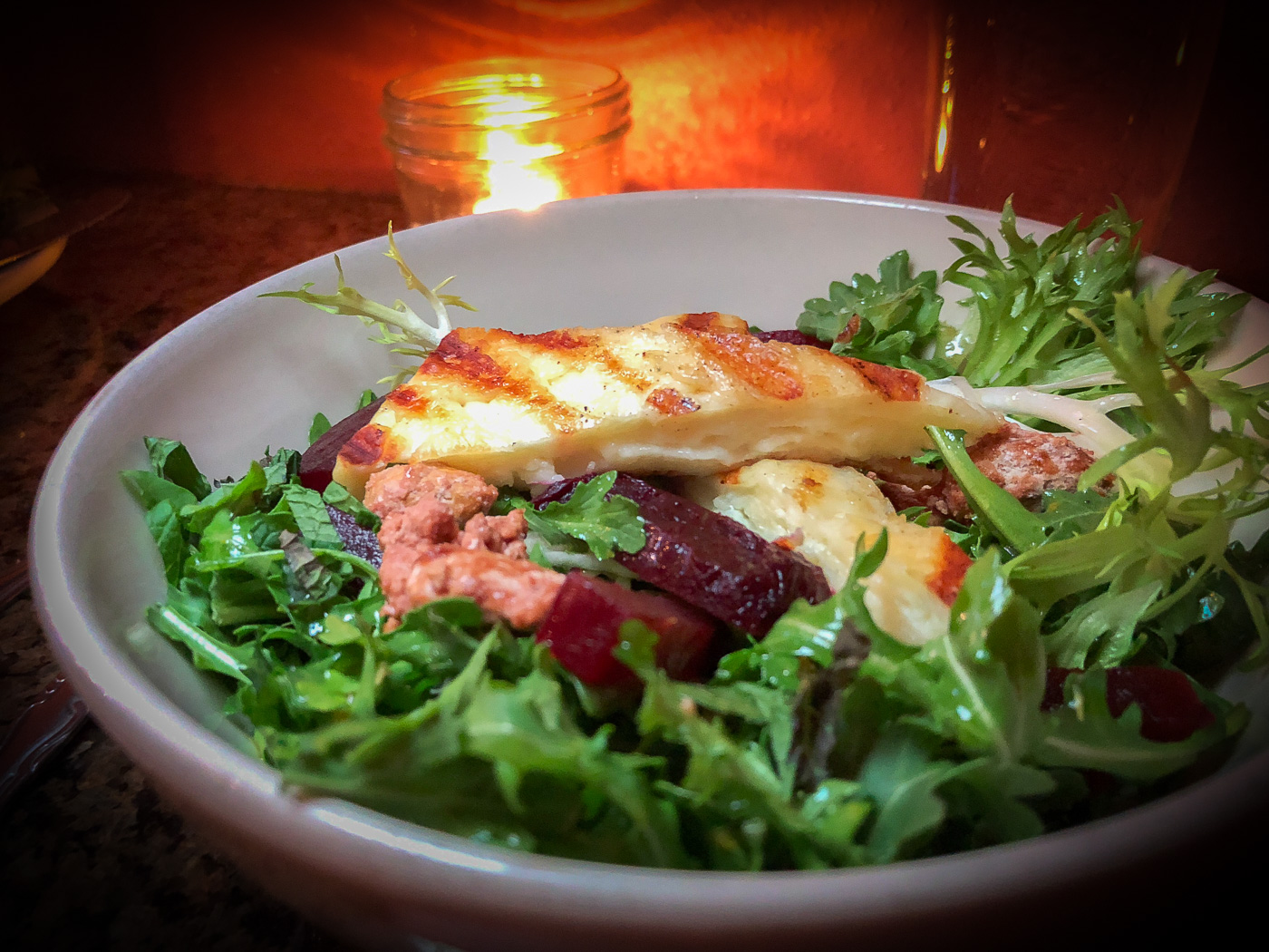 Bowl of salad with beets and grilled haloumi cheese