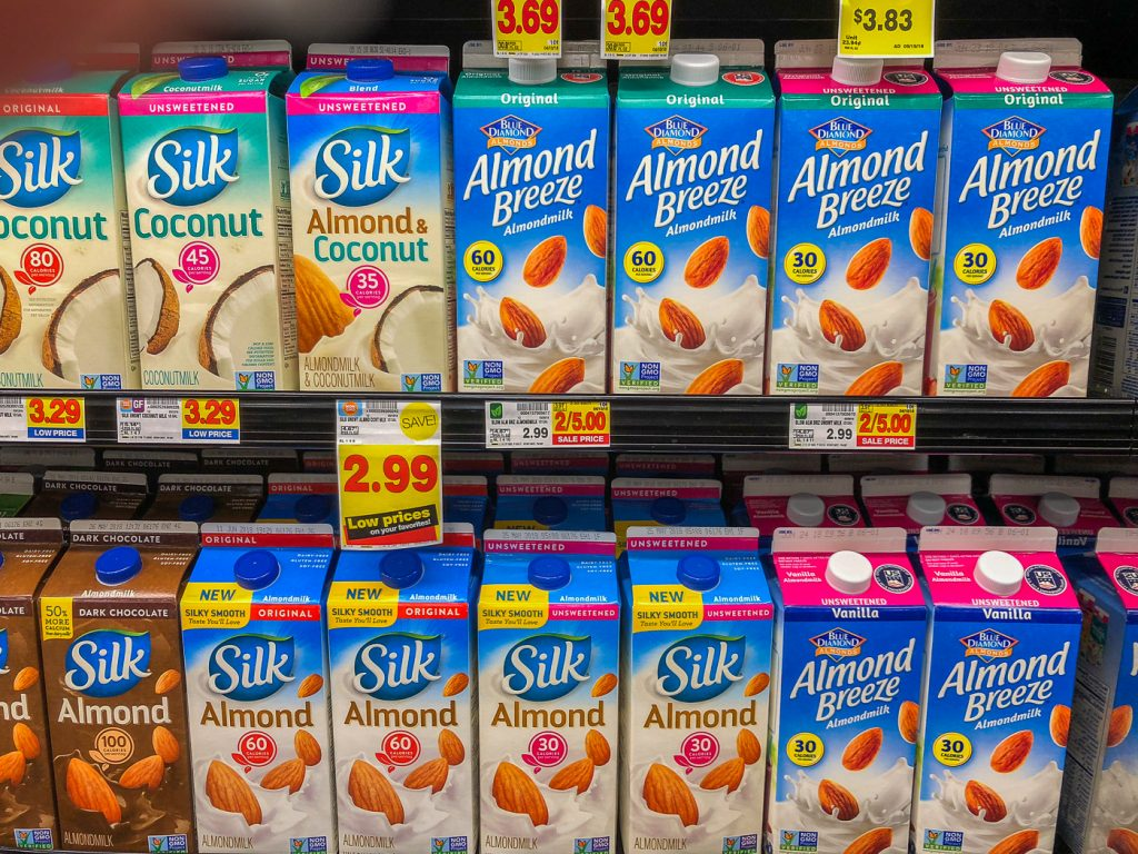 Grocery store refrigerated shelf of non-dairy milk cartons