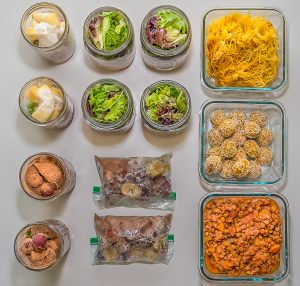 Overhead shot of mason jars and glass containers with salad and smoothie ingredients