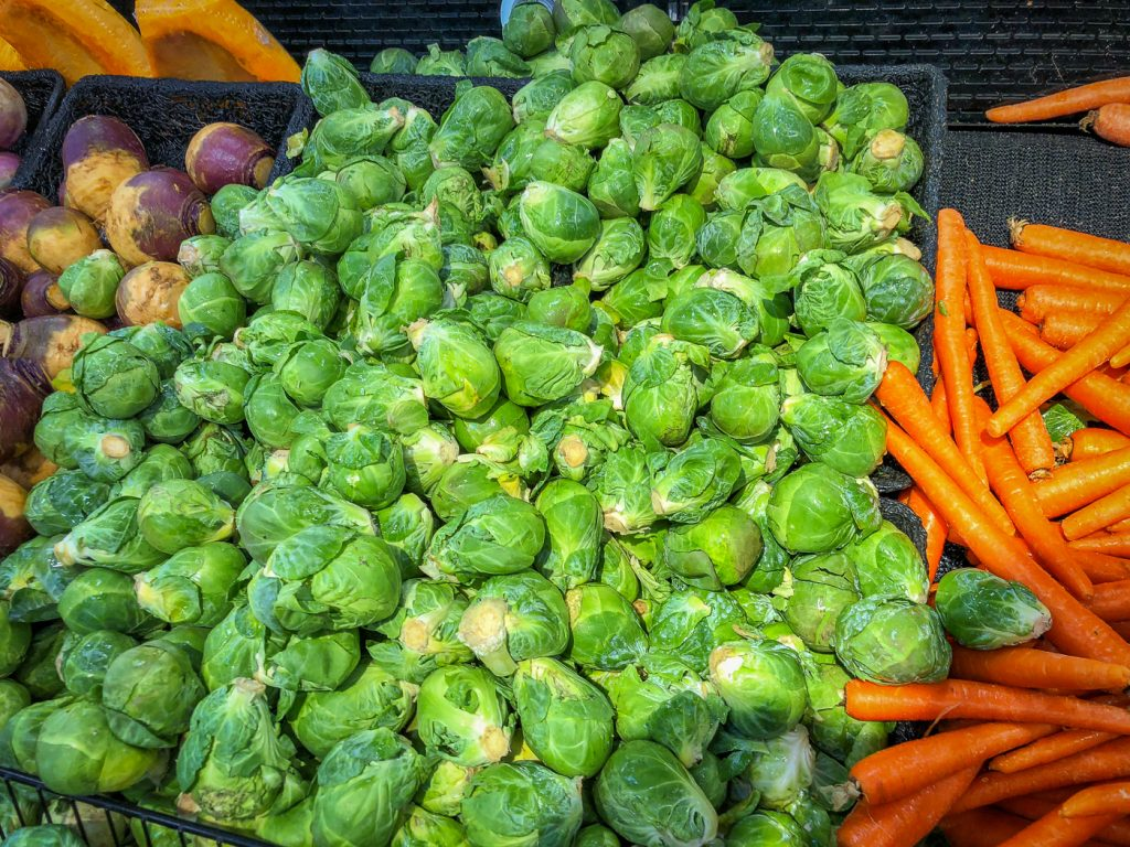 Piles of Brussels sprouts and carrots in a grocery store produce section