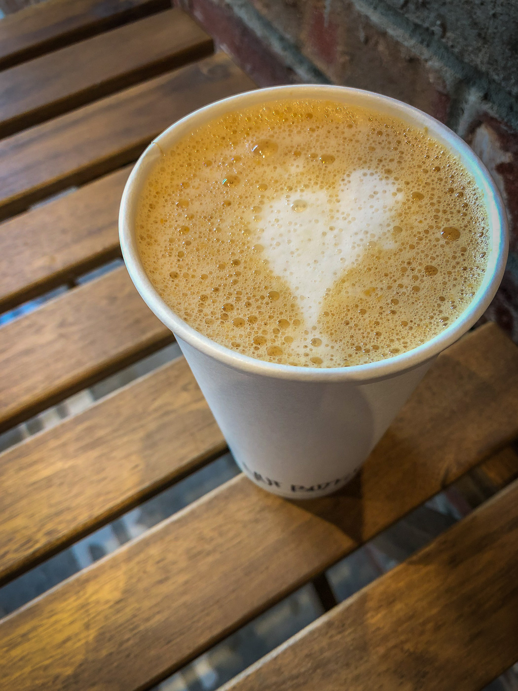 Top down picture of a latte in a paper cup with a heart drawn in the foam