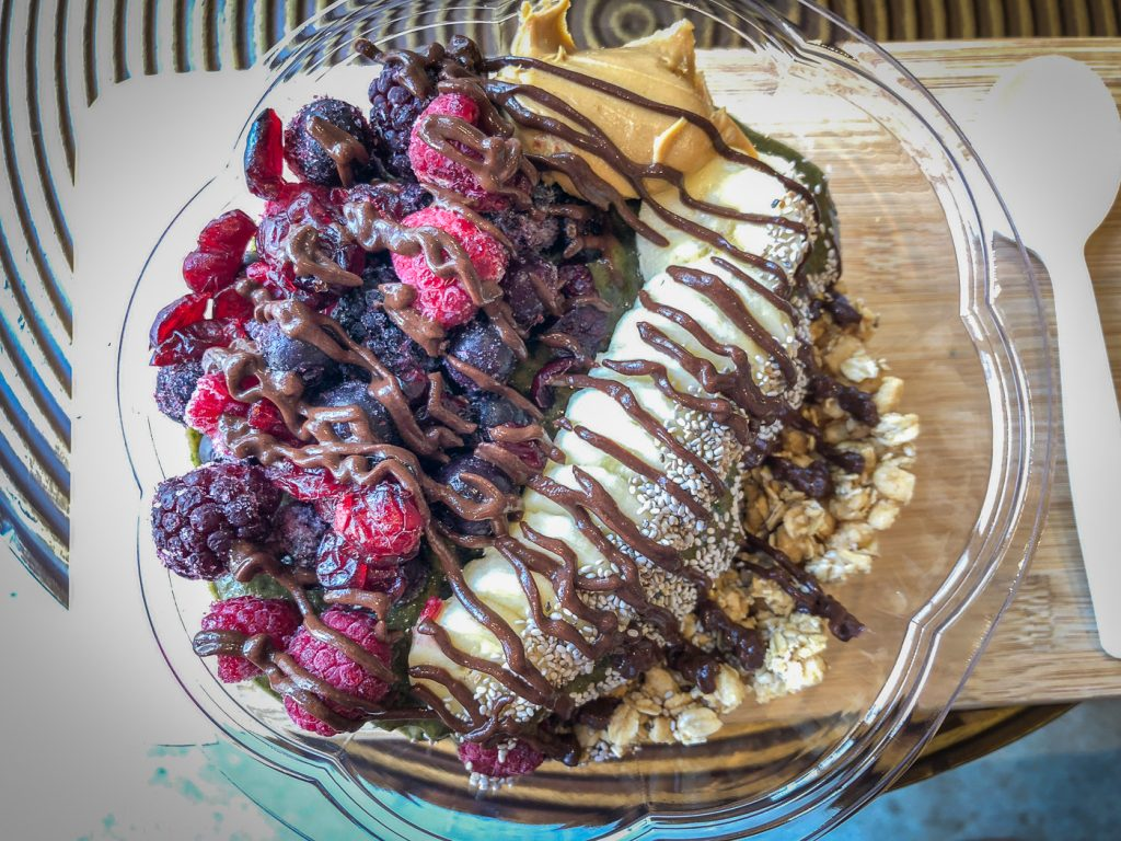 Overhead shot of a smoothie bowl covered with fruit, granola and chocolate drizzle