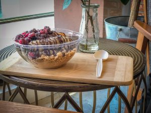 Plastic bowl filled with smoothie and fruit on a wooden tray on a table