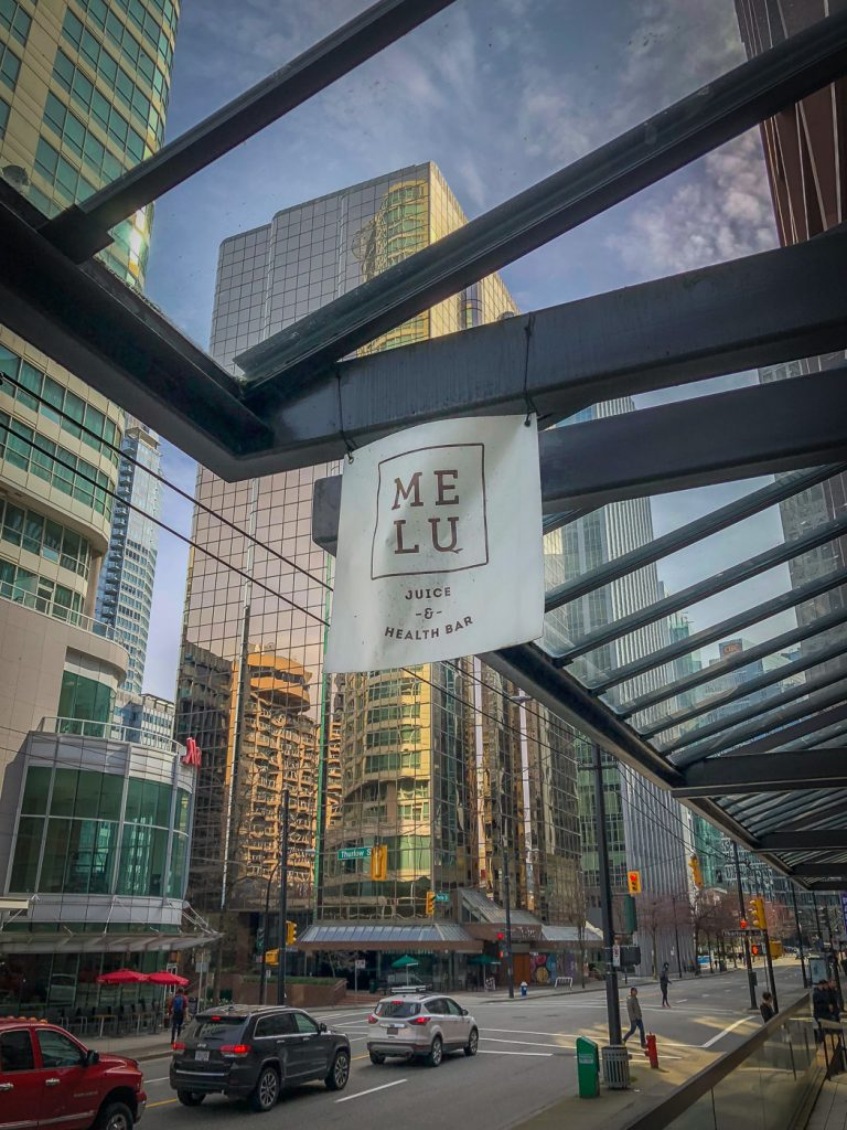 Glass covered walkway with a sign hanging down for Melu Juice