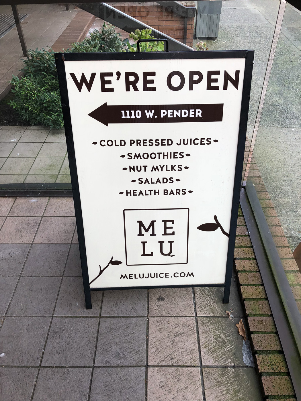 Sandwich board sign on patio advertising Melu Juice