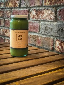 Bottle of green juice on a wooden table in front of a brick wall
