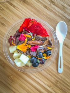 Plastic bowl filled with apples, blueberries, strawberries, dark chocolate and edible flowers