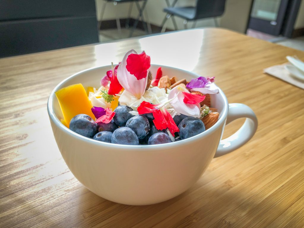 Large tea cup filled with edible flowers and fruit on a bamboo table