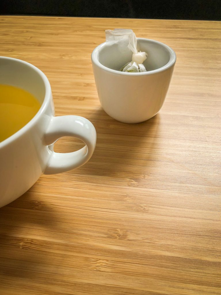 Tea cup and a small cup to hold the teabag on a bamboo table