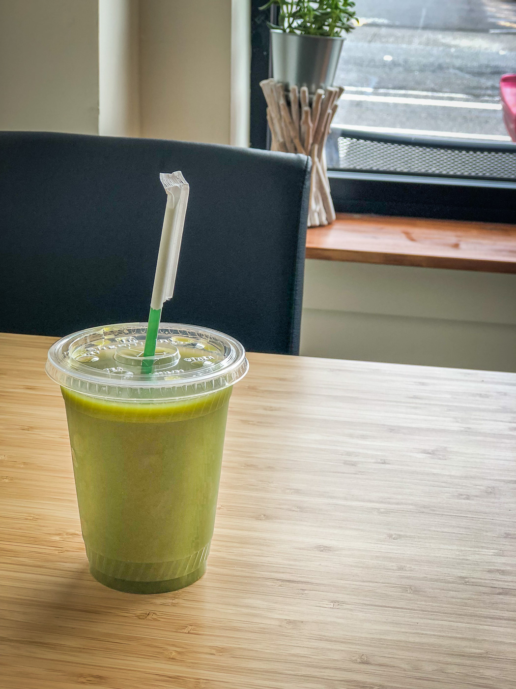 Plastic cup on a bamboo table full of green juice