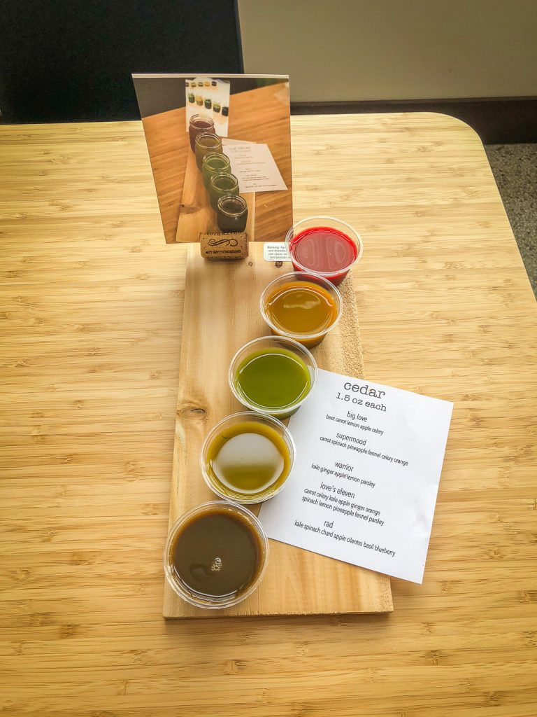 5 small cups of colorful juice on a cedar plank