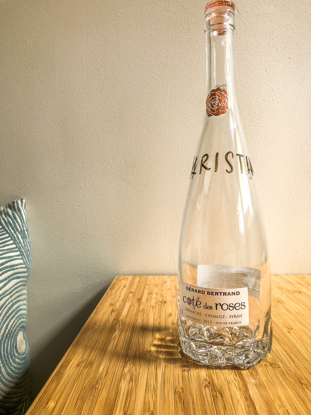 Glass bottle on bamboo table that has the name Kristine written on it