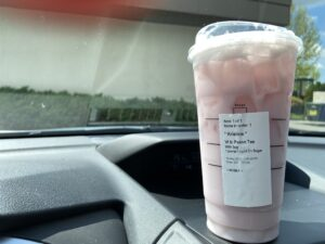 Cup of Starbucks iced tea on the dash of a car