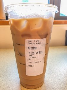 Starbucks cup with order sticker flat white