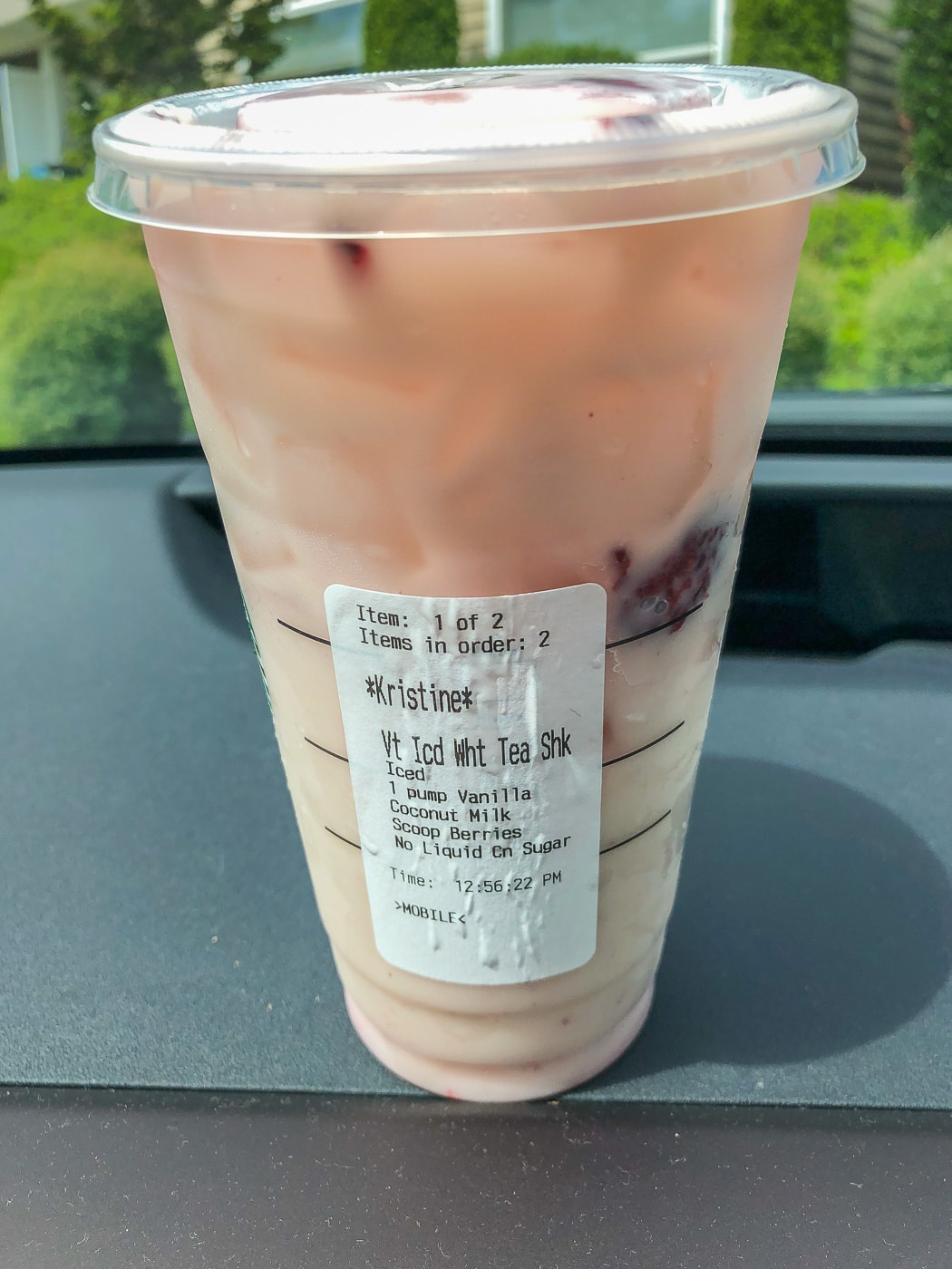 Starbucks cup with order sticker on car dashboard white tea