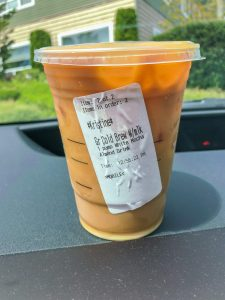 Starbucks cup with order sticker on car dash