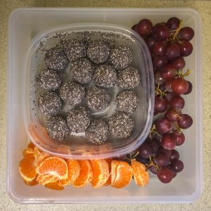 Plastic container filled with brownie bites and fruit