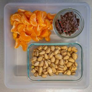 Plastic container filled with orange segments, pistachios and chocolate bark