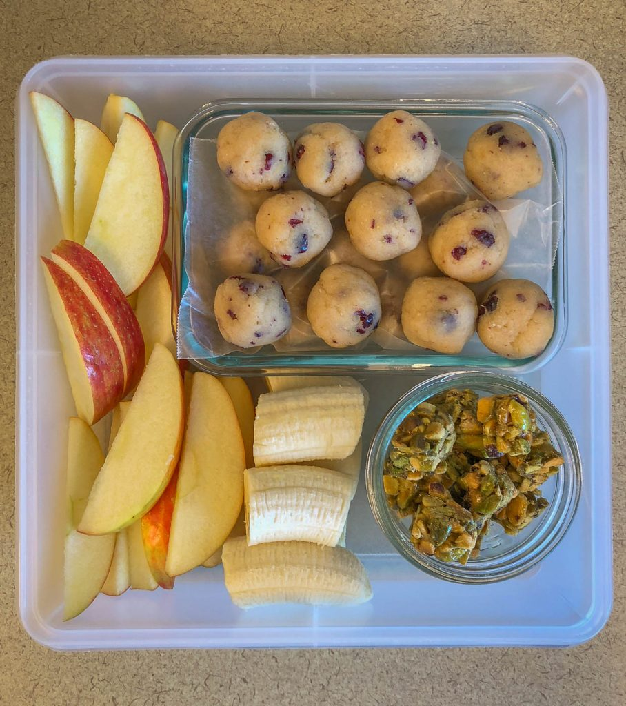 Plastic container filled with fruit, nut bites and energy balls