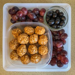 Plastic container filled with rice crispy balls, fruit and olives