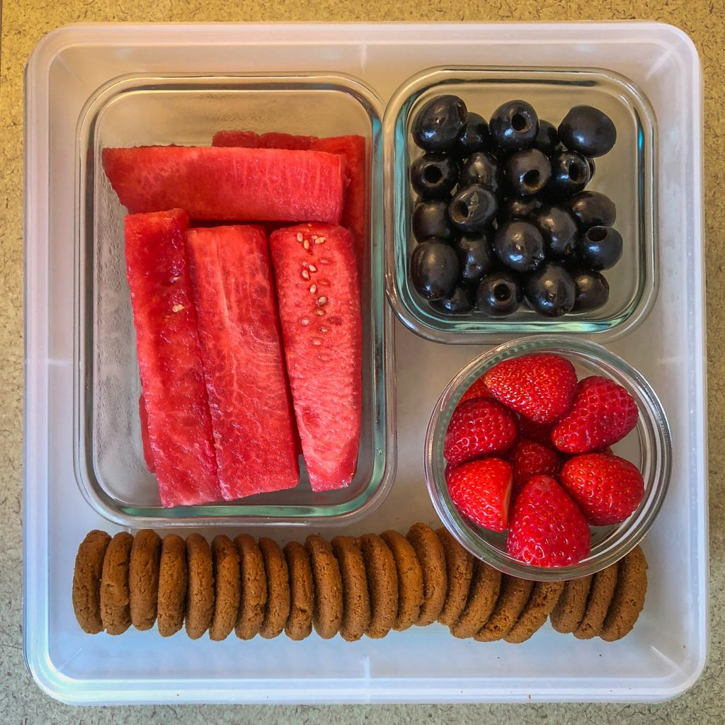 Plastic container filled with fruit and cookies