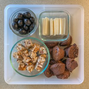 Plastic container with nut clusters, olives, cheese, and brownie bites
