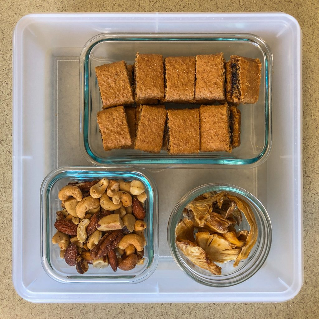 Plastic container with fig bars, nuts and dried fruit