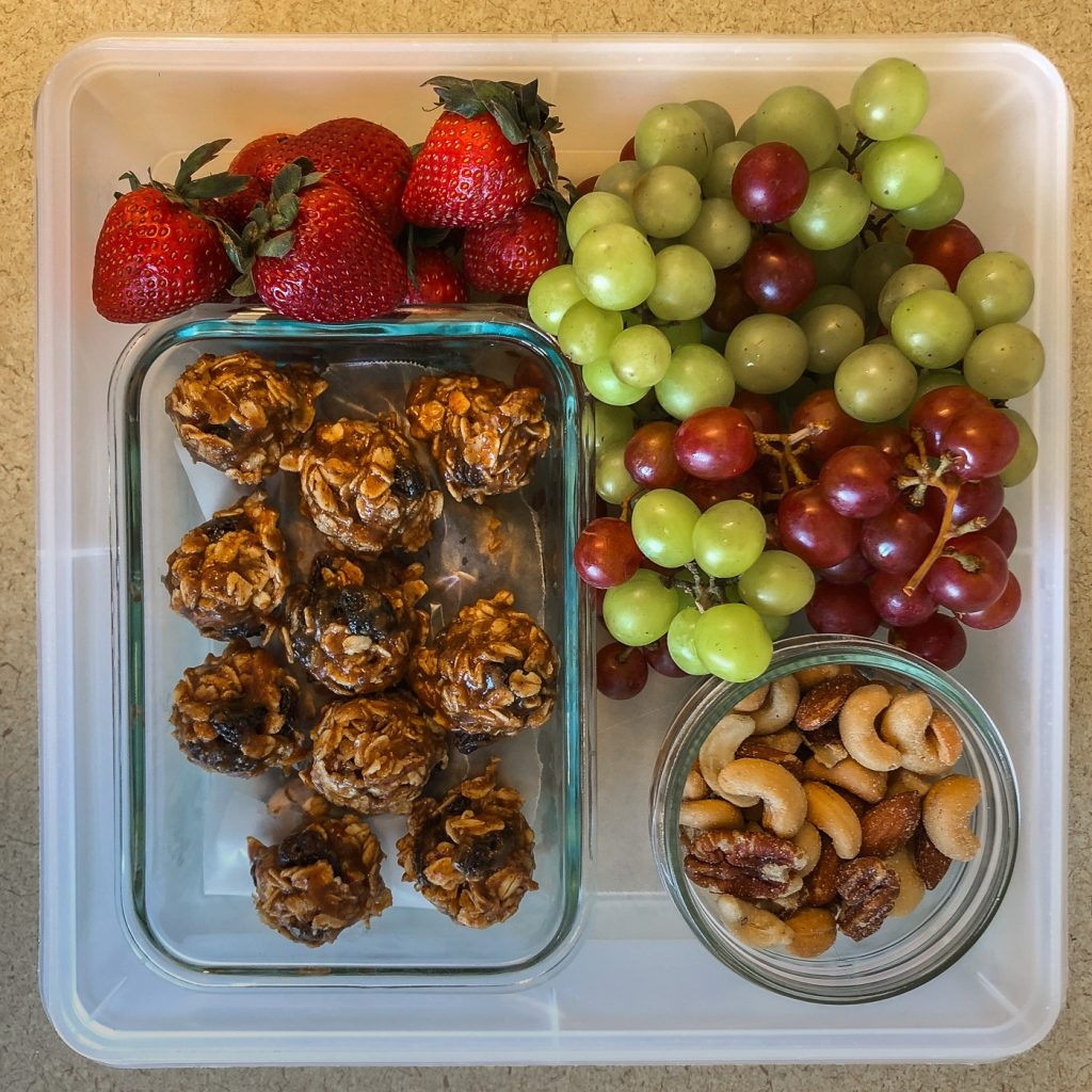 Plastic container filled with fruit, cookies and nuts