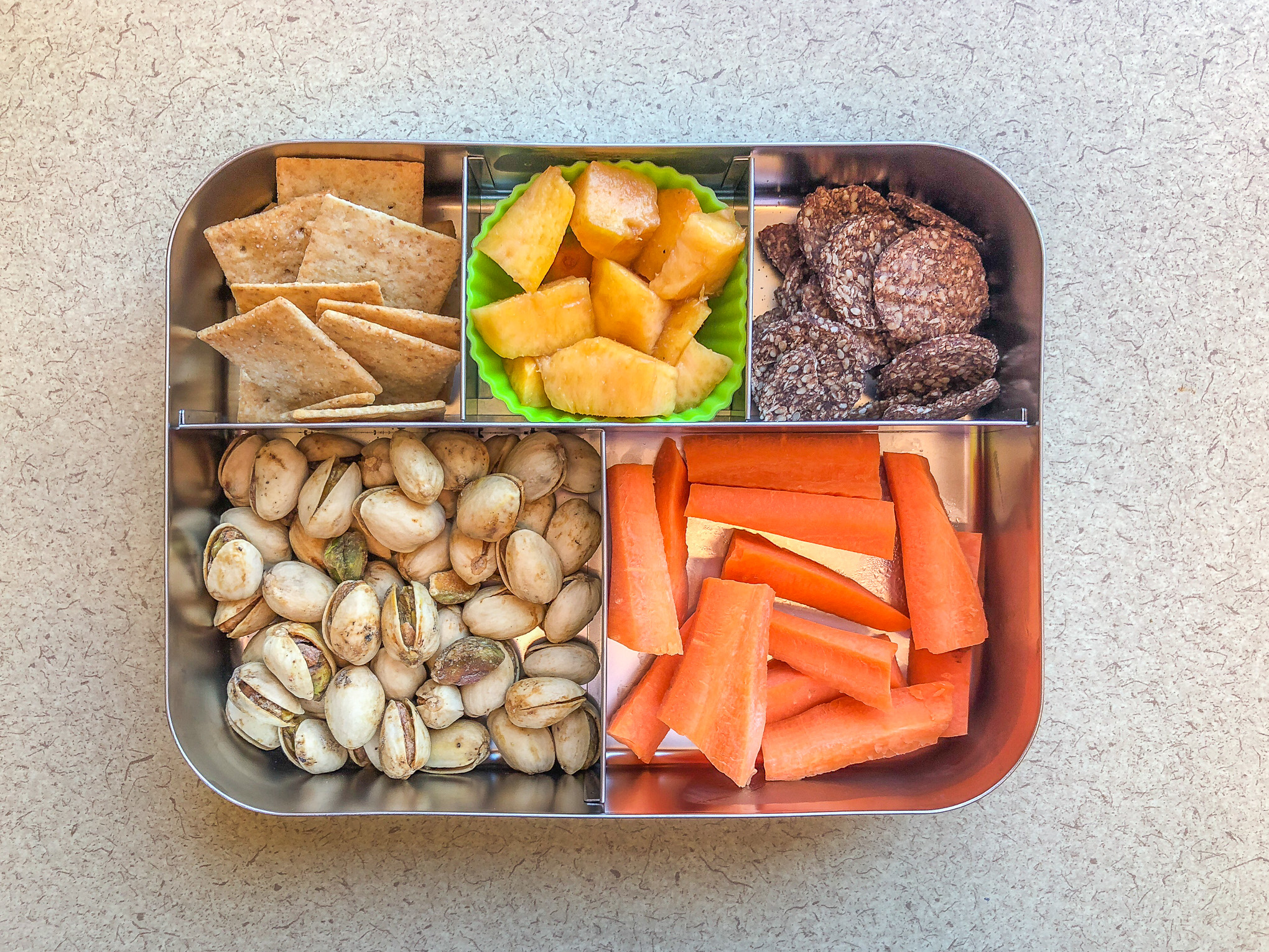 Metal lunch box filled with crackers and pistachios