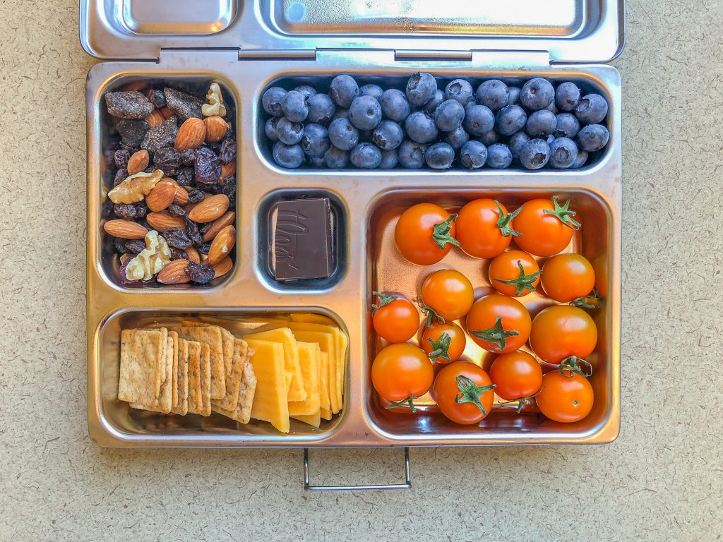 Metal lunchbox filled with berries and tomatoes