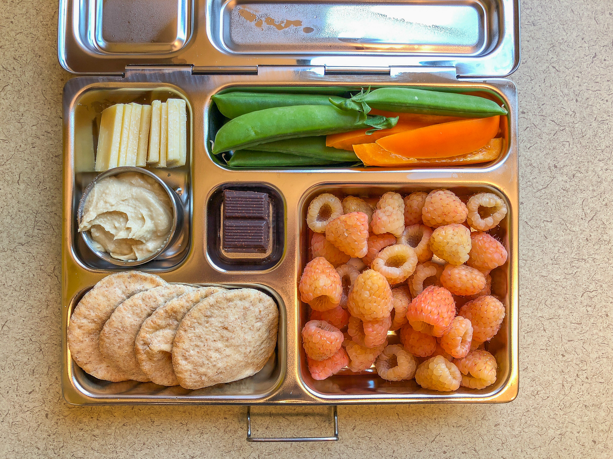Metal lunch box filled with fruit and veggies