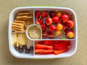 Plastic bento lunch box filled with fruit and veggies