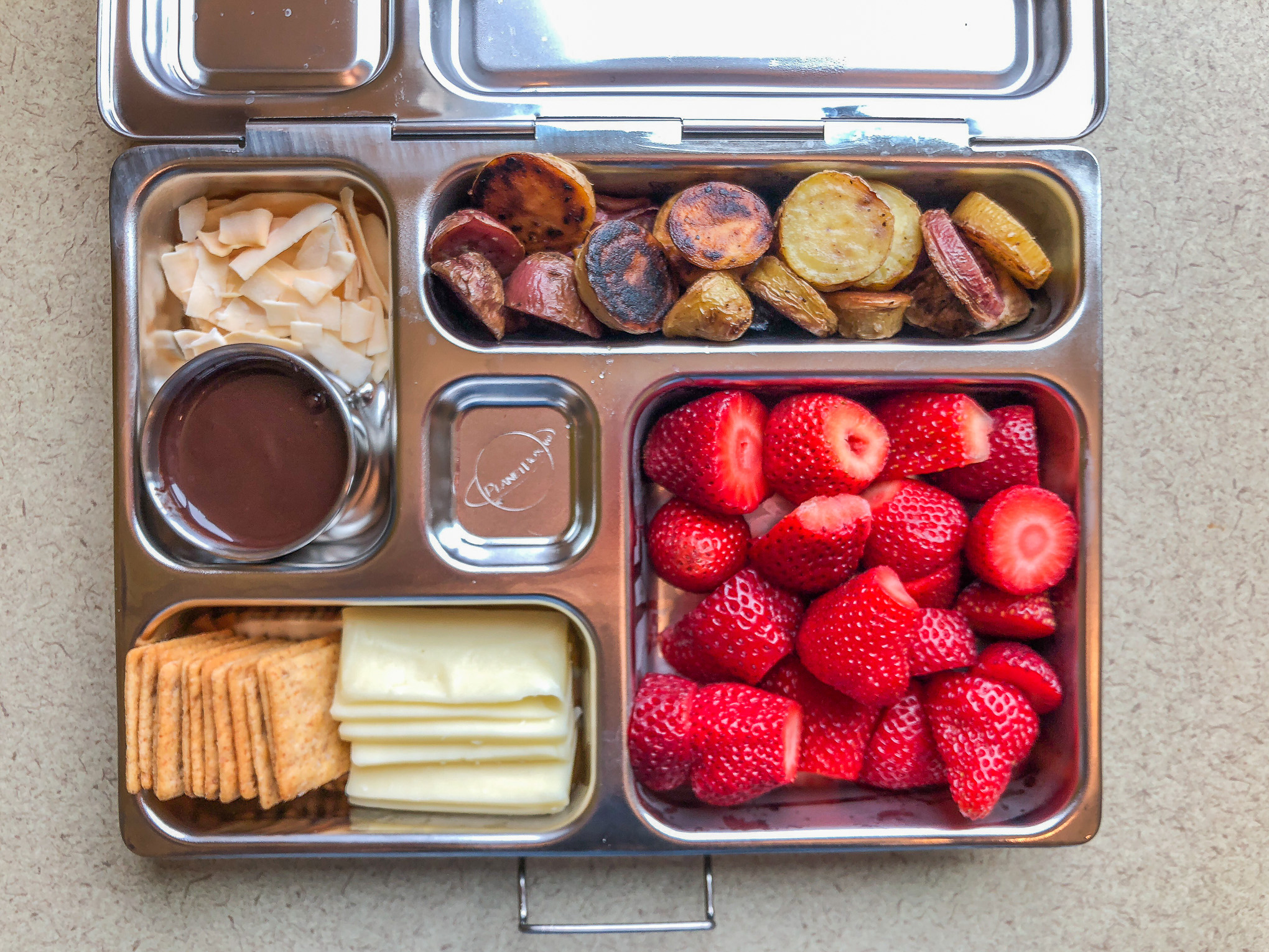 Metal lunchbox filled with fruit and veggies