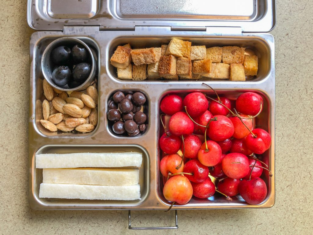 Metal lunch box filled with fruit and tofu
