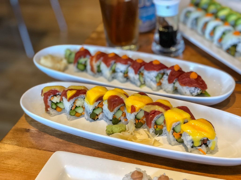 Two oval plates filled with colorful sushi rolls