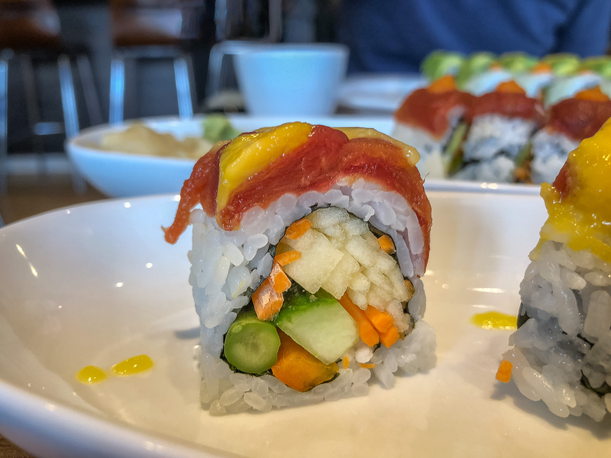 Close up picture of a sushi roll topped with tomato