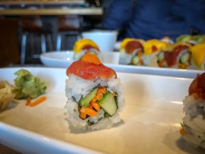 A single sushi roll topped with tomato