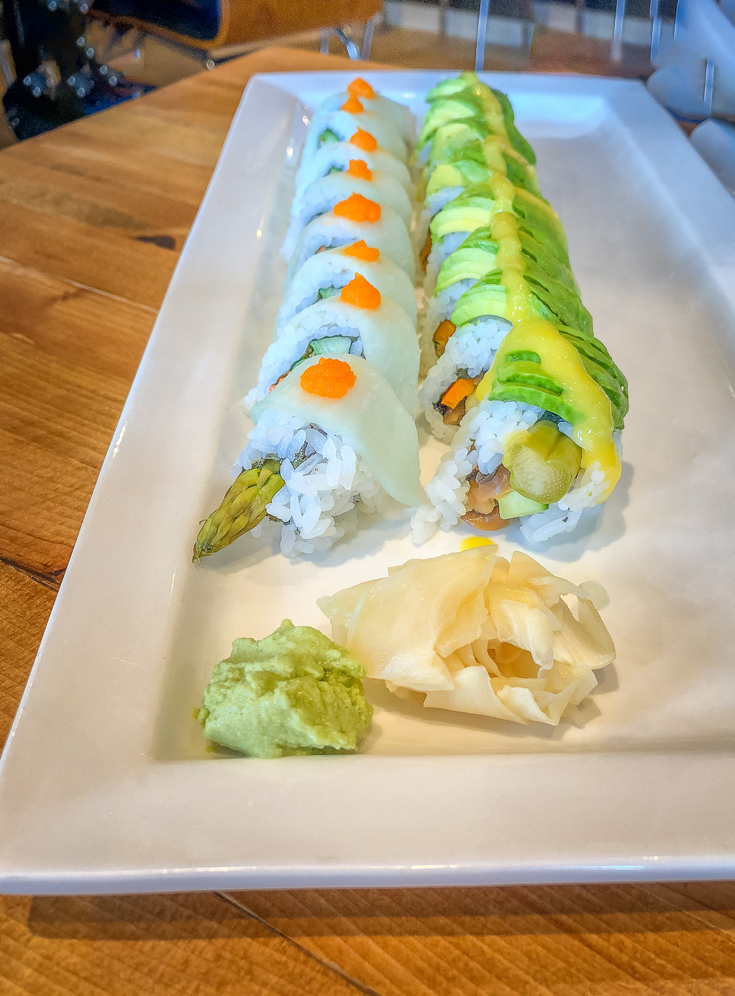 Oblong white plate with two rows of sushi rolls