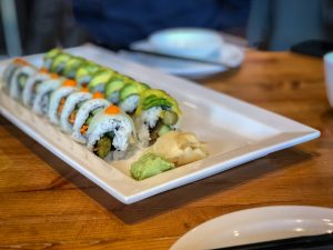 Oblong plate with two rows of sushi, garnished with wasabi and ginger