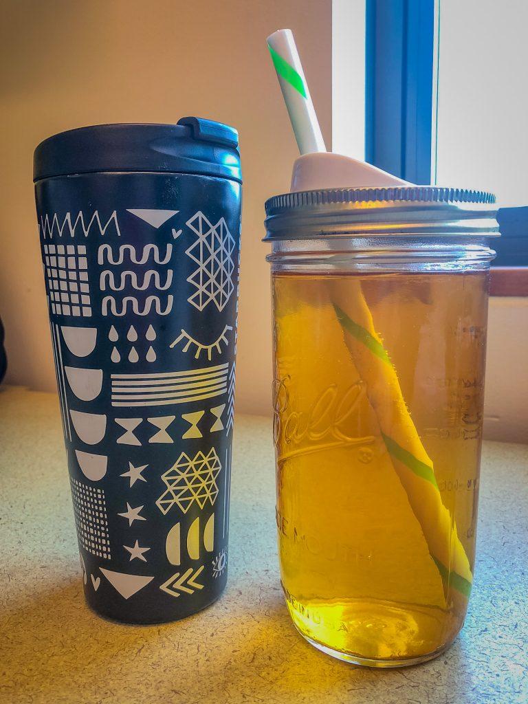 Travel mug and canning jar full of hot tea and iced tea