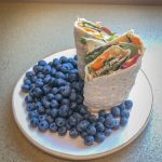 Wrap sandwich on a plate with blueberries