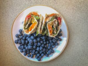 Wrap sandwich standing up on a plate surrounded by blueberries