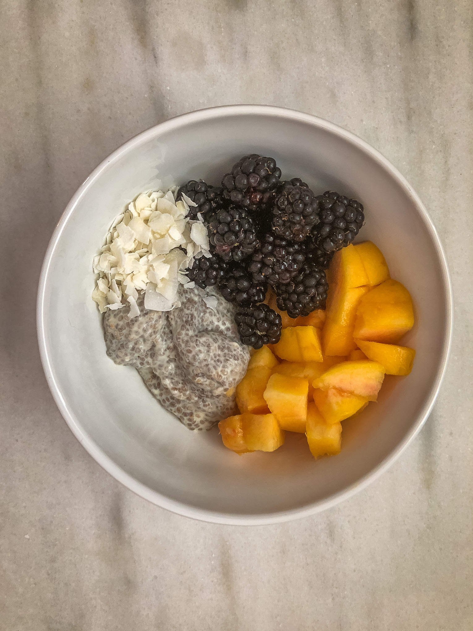Bowl of chia pudding topped with fruit and coconut