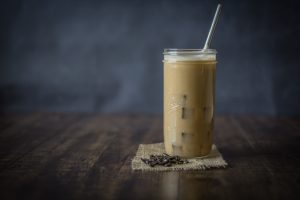 Mason jar filled with iced coffee and a straw
