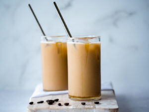 Two glasses full of iced coffee with straws
