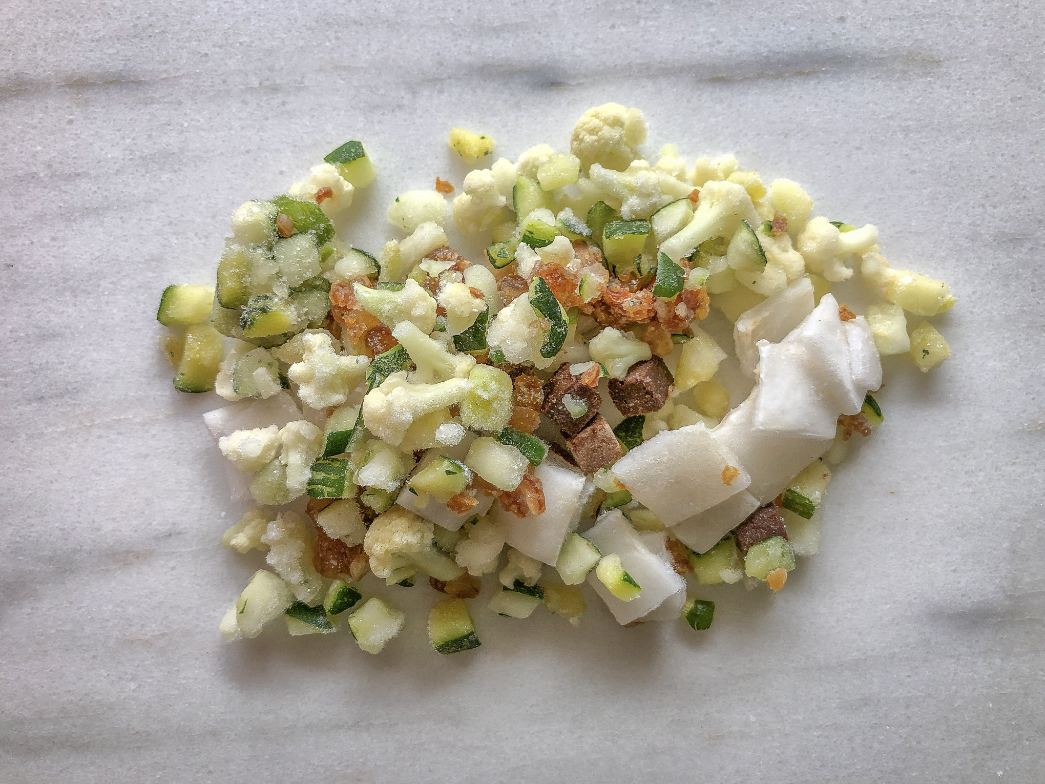 Cauliflower, coconut, zucchini and other frozen smoothie ingredients on marble