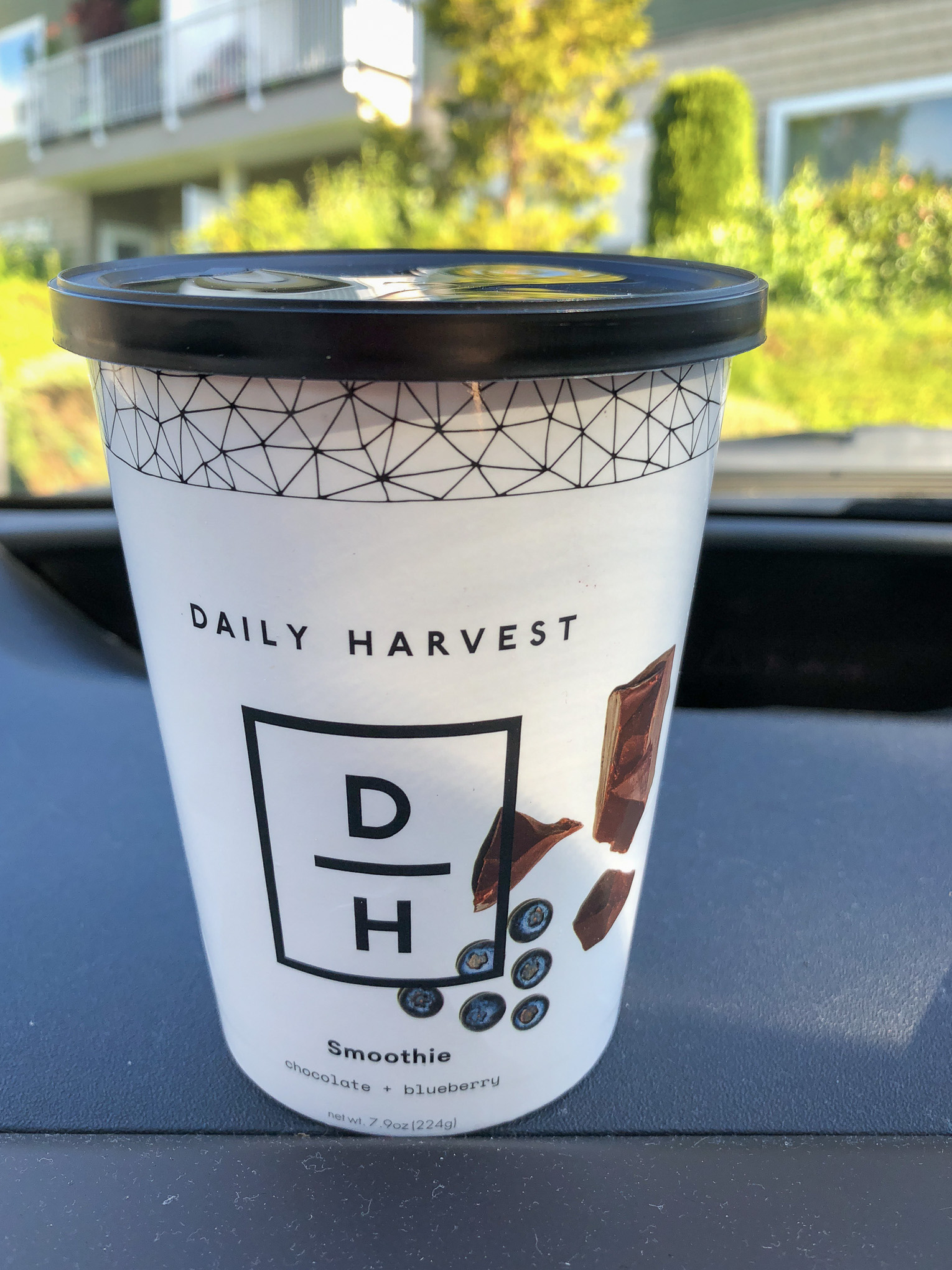 Paper cup on car dashboard with smoothie inside