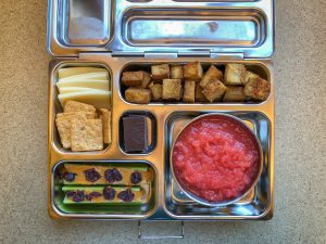 Bento box filled with tofu, applesauce and cheese