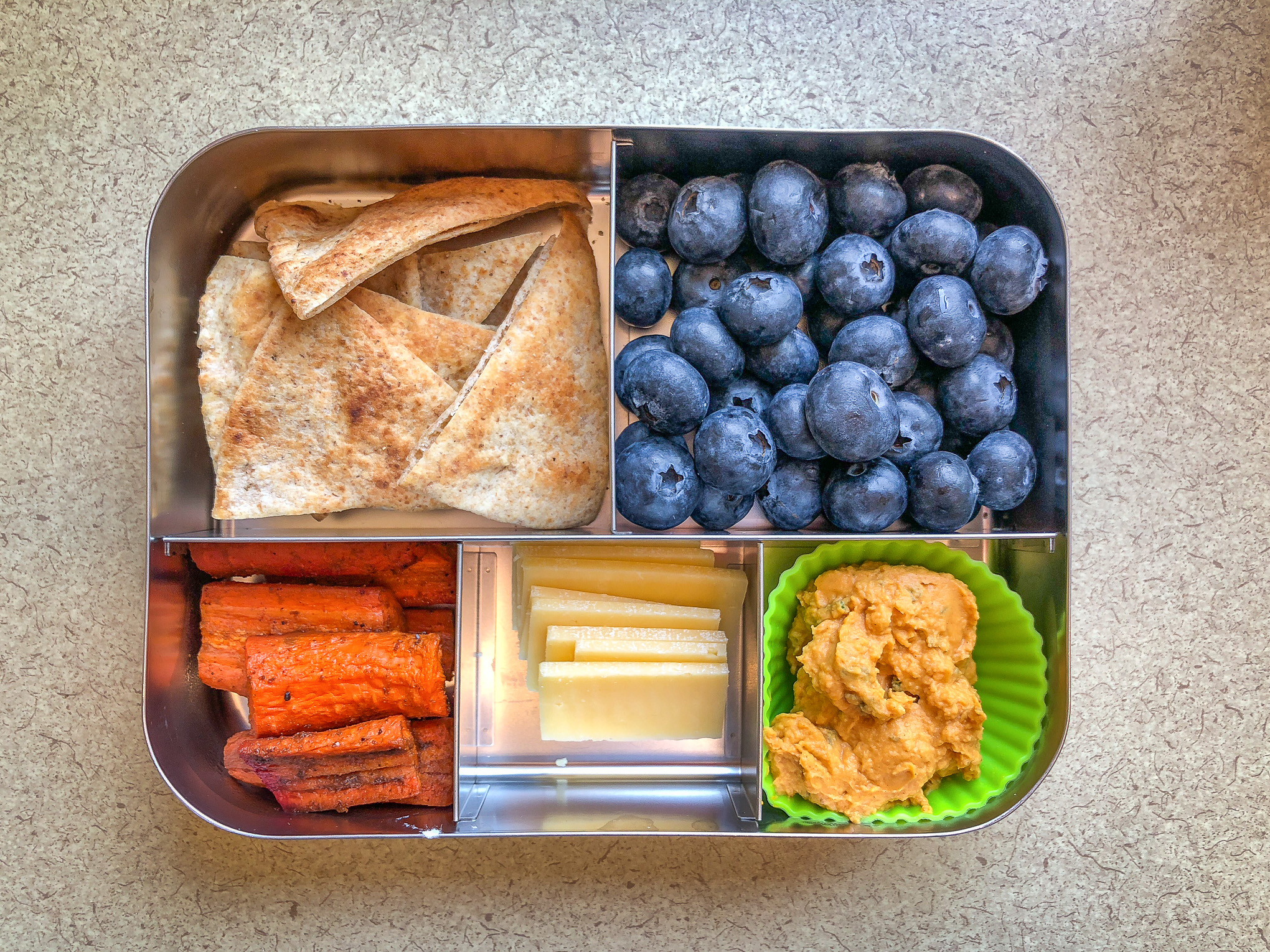 Bento box filled with pita chips and fruit